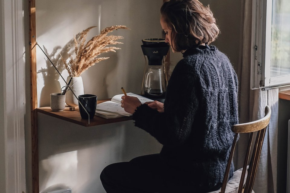 Young woman is sitting at a desk with her notebook and coffee.