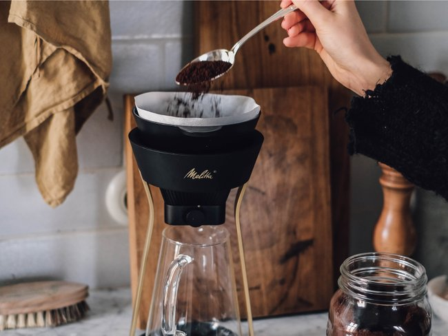 Ground coffee is filled with a spoon into a manual coffee maker.