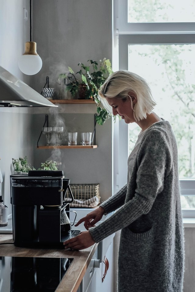 Blonde woman standing in front of the kitchenette with the first electrical Pour Over system by Melitta®.