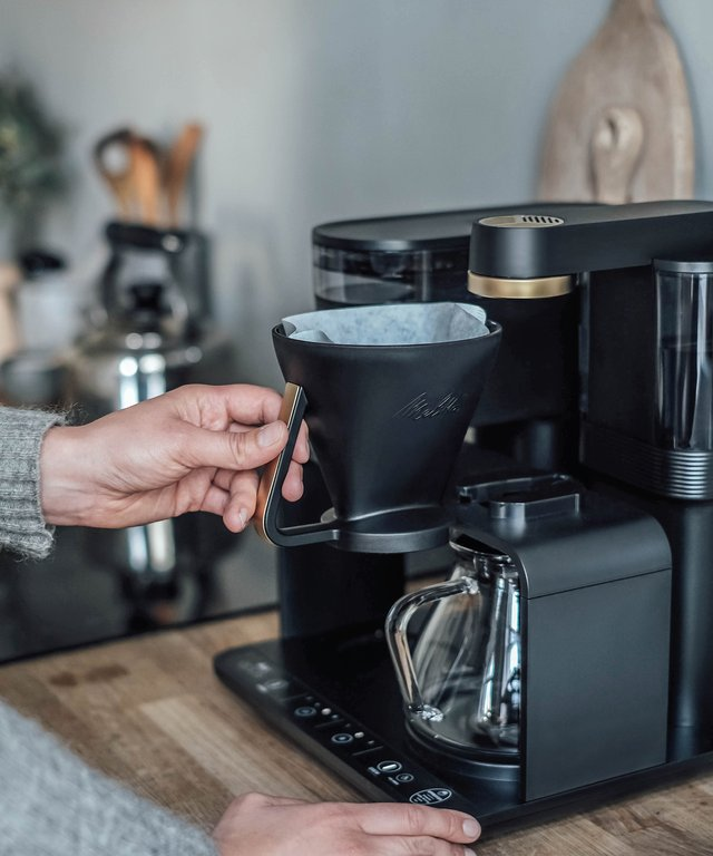 Woman inserts a coffee filter into a Melitta® EPOS®.
